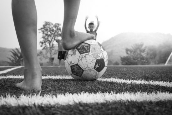 Boy with foot on well used soccer ball. Boy in background holds up arms. Black and white photo.