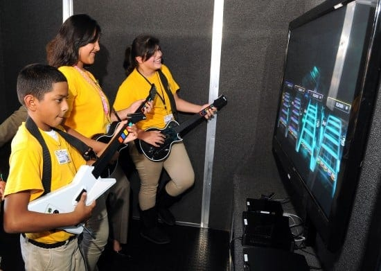 From left: Students Isaac Zuniga, Alondra Garcia and Abigal Garcia play Guitar Hero in the Game Truck following the RockIt! press conference at Marshall Middle School Thursday Oct. 11,2012. (Dave Rossman photo)
