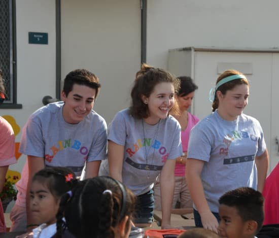 Service with a smile. Riley and two Rainbow Pack volunteers at a backpack giveaway (courtesy).