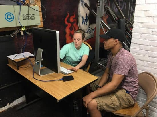 A female volunteer helps a boy in a baseball cap work at a computer on his resume