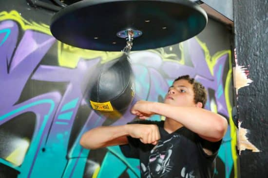 A boy punching a speedbag bag