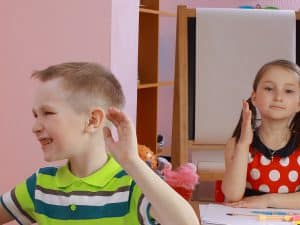 Squirmy Boy with ADHD seated at desk in front of girl politely raising her hand shows it's hard to manage ADHD in the classroom