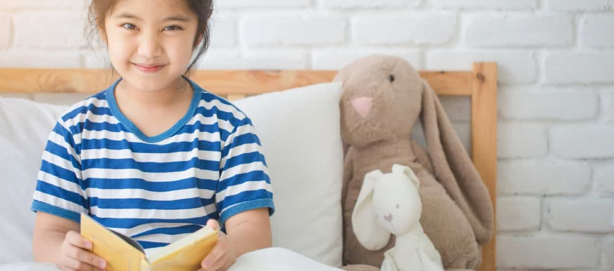 Sleep Duration a Factor in Childhood Obesity. Smiling Chinese Girl reading in bed, stuffed bunny nearby.