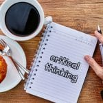 "cup of coffee and danish next to hand writing on a notepad ""critical thinking"""