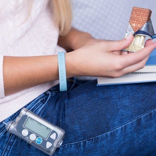 Diabetic teen with insulin pump eating source of glucose