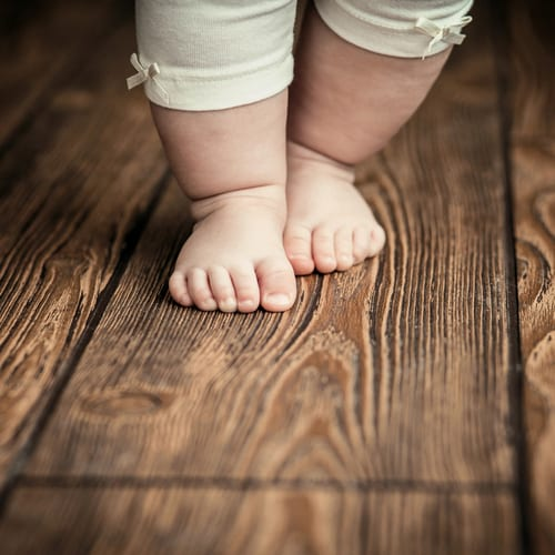 A baby's fat little feet on a wooden floor