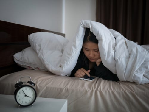 Asian teen texting on her smartphone under the covers