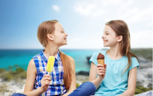 Two young girlfriends eating treats on the beach, smiling at each other.