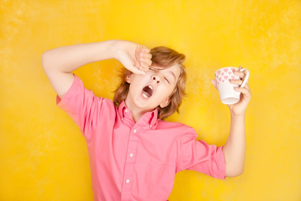 ADHD symptoms or just sleep deprivation? A boy yawns, coffee cup in hand.