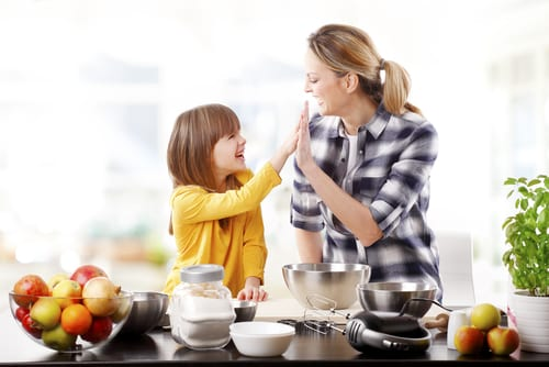 Mother and daughter high five as they prepare recipes in the kitchen