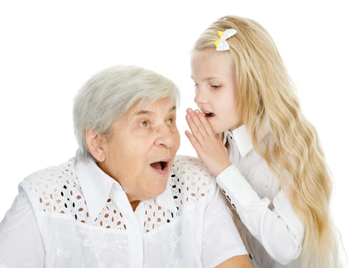 Child whispers in the ear of shocked seated elderly woman