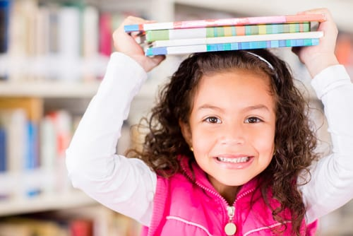 little girl enjoys summer library fun with books on head