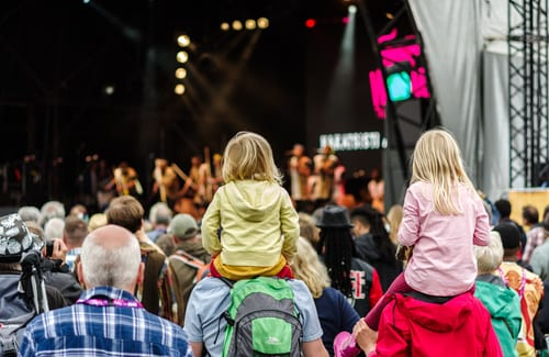 children on parents' shoulders at concert