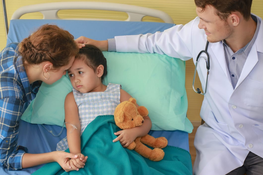 Mother holds hand of sick child in hospital bed as ER doctor in white coat with stethoscope looks on.