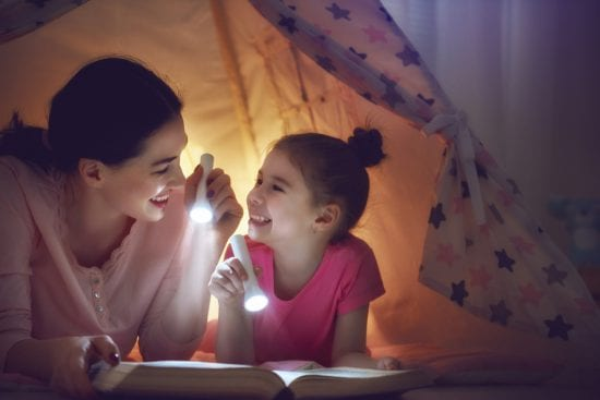 Mother Reads to Daughter in tent with both holding flashlights and smiling
