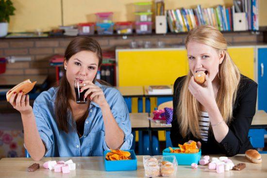 Two Schoolgirls eat junk food and drink soda