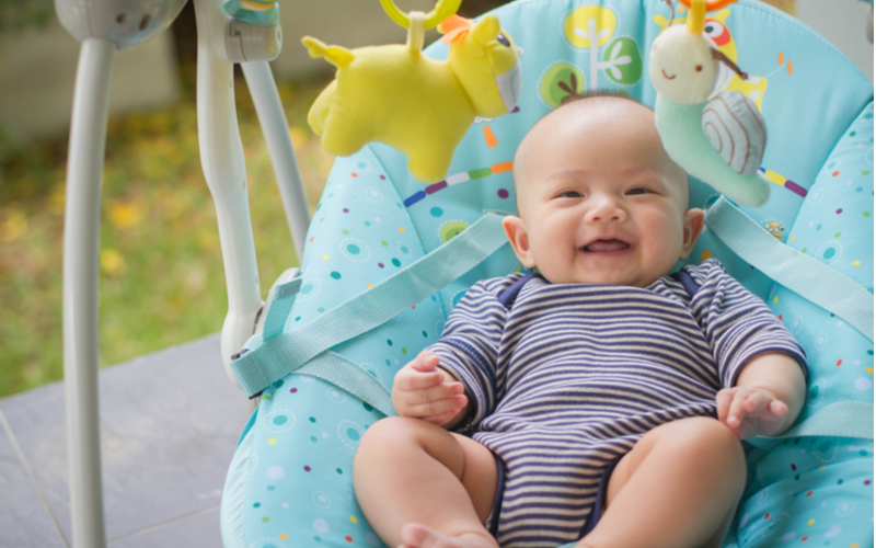 smiling asian baby in bounce seat
