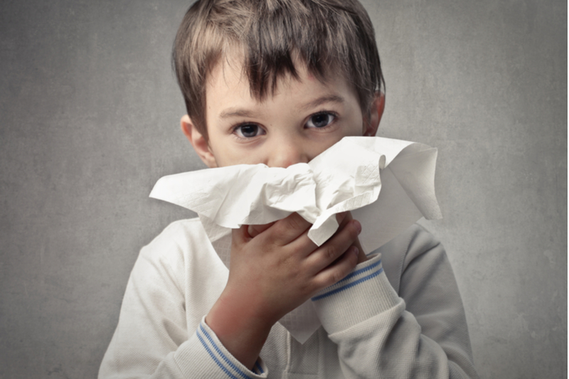 Little boy positions tissue for nose blowing