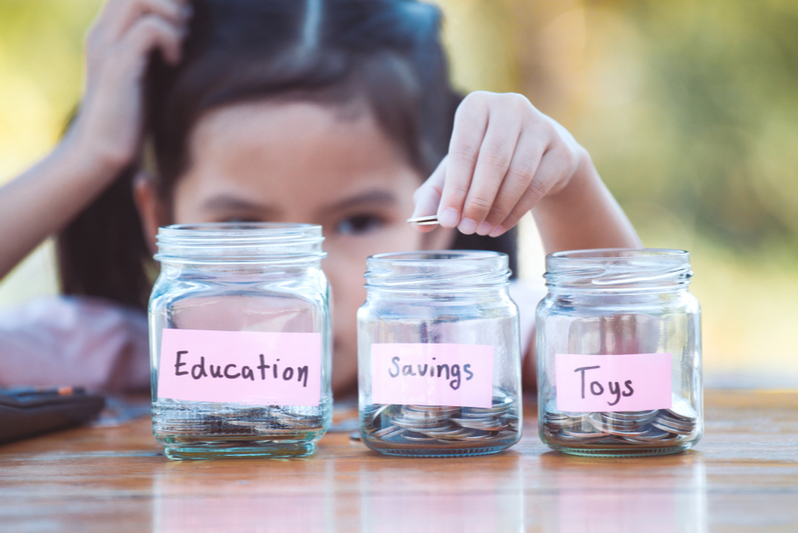 Girl puts allowance into jars labeled education savings toys