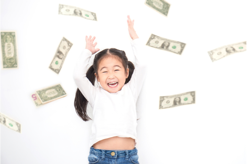 Happy pigtailed Asian girl throws money in air