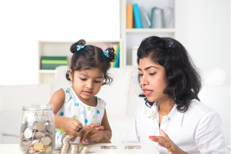 Indian mom helps little girl count coins