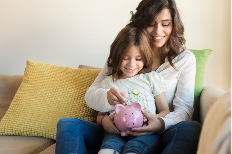 Mom helps little girl put coins in piggy bank