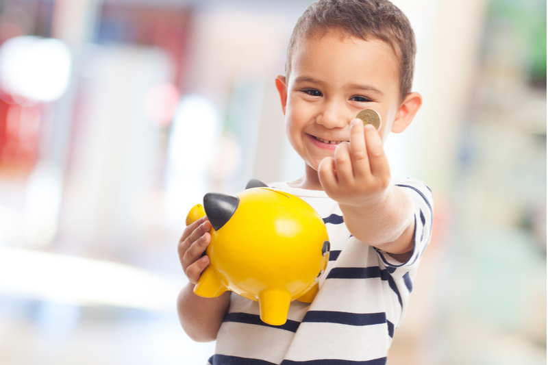 Smiling boy shows coin he will put in bright yellow piggy bank